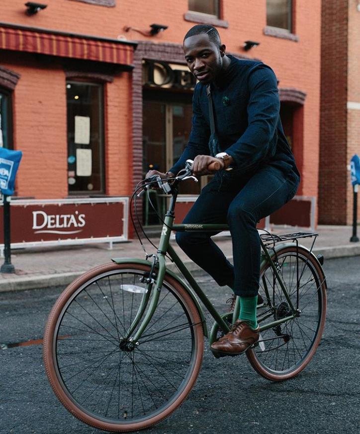 Ciclista montando una bicicleta verde crítica mens