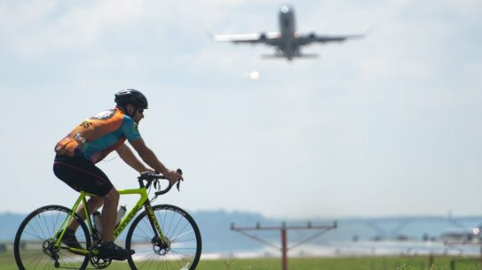 man rides a bicycle past an airplane taking off from ronald news photo 1026509710 1550252950